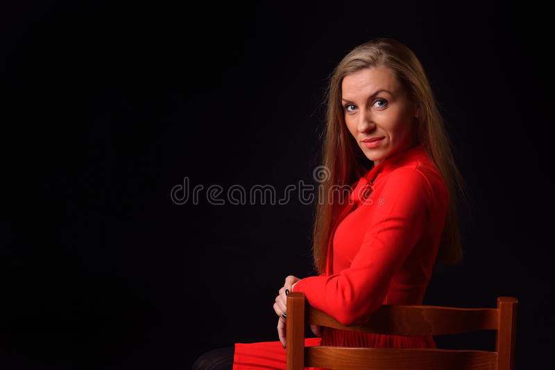 Beautiful blonde young woman in a red dress is sitting on a chair posing in a studio on a black background royalty free stock photos