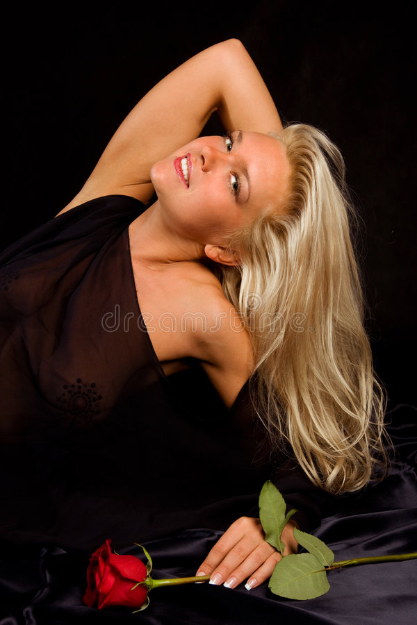 Beautiful blonde young woman with red rose stock photo