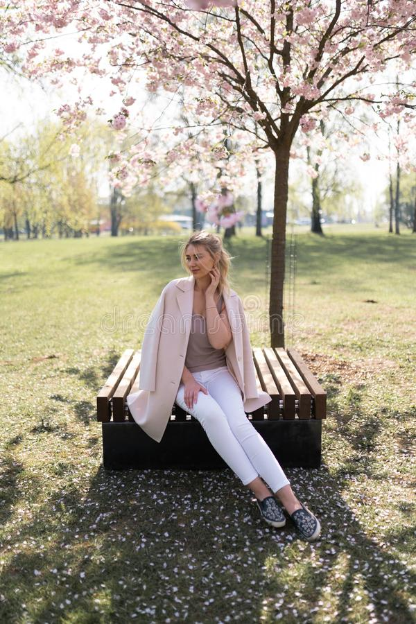 Beautiful blonde young woman in Sakura Cherry Blossom park in Spring enjoying nature and free time during her traveling royalty free stock image