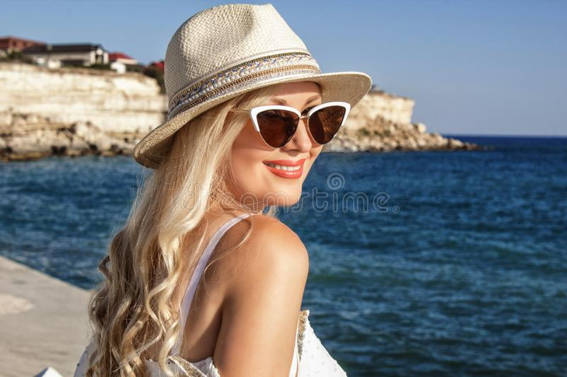 Beautiful blonde young woman smiling beautifully, with long hair in a hat at the sea, portrait. royalty free stock photo