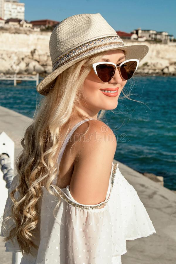 Beautiful blonde young woman smiling beautifully, with long hair in a hat at the sea, portrait. stock photo