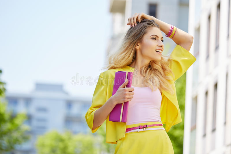 Beautiful blonde young woman walking on the street royalty free stock images
