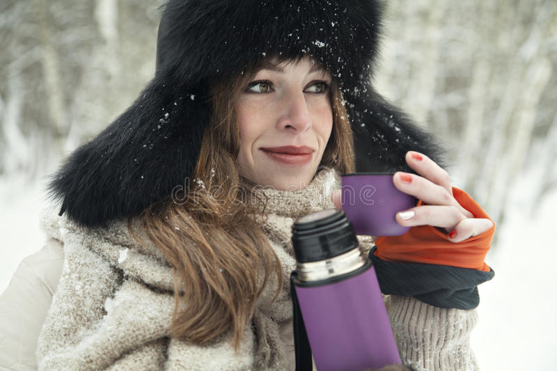 Beautiful blondy girl drink hot tea in a thermos in snowy forest royalty free stock images
