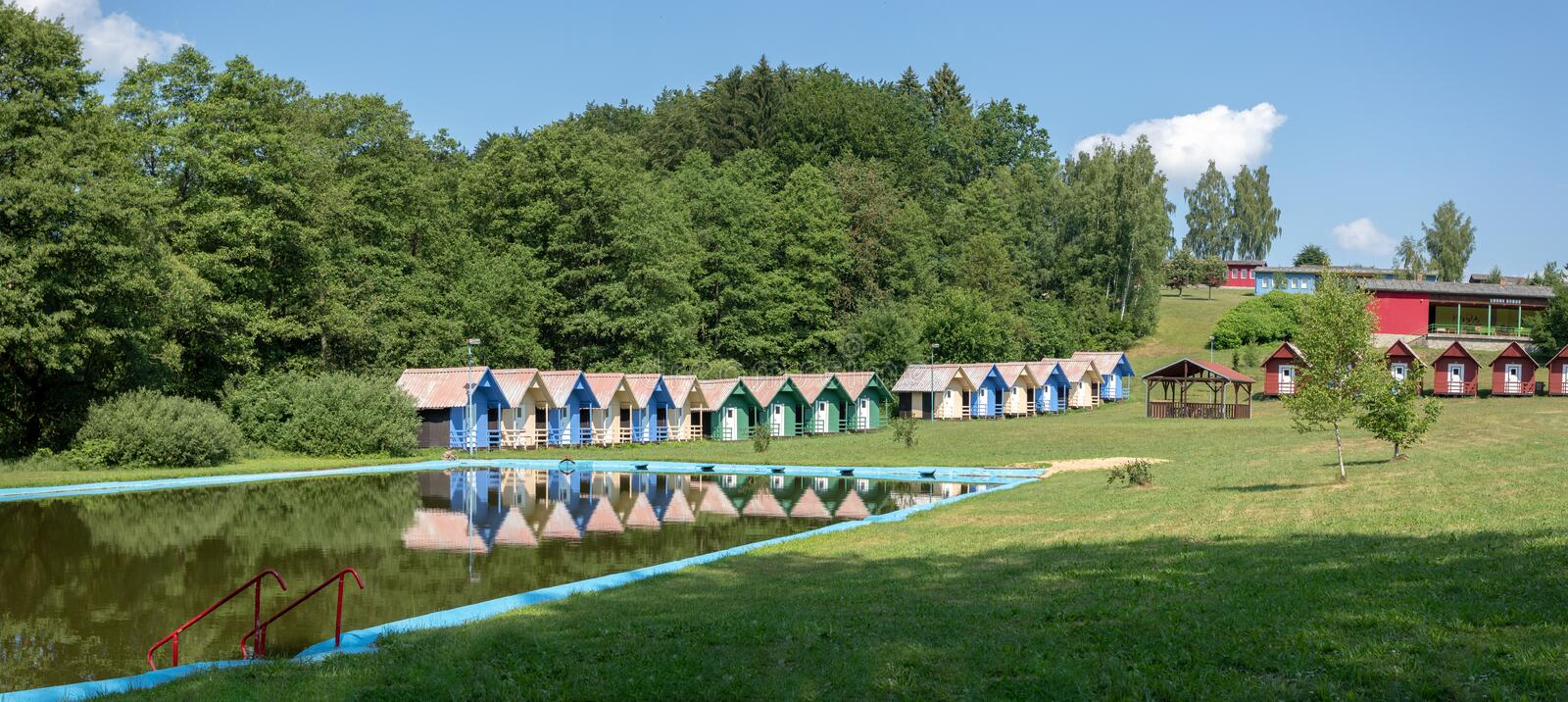 Children`s chalets camp in summer. Beautiful blue chalets in a summer camp for children situated near pond stock photos