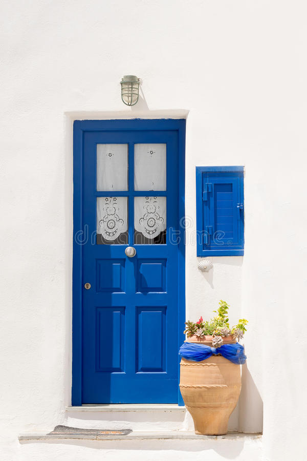Beautiful blue door with a pot outside at Paros island in Greece. A traditional cyclades outside of a house. stock image