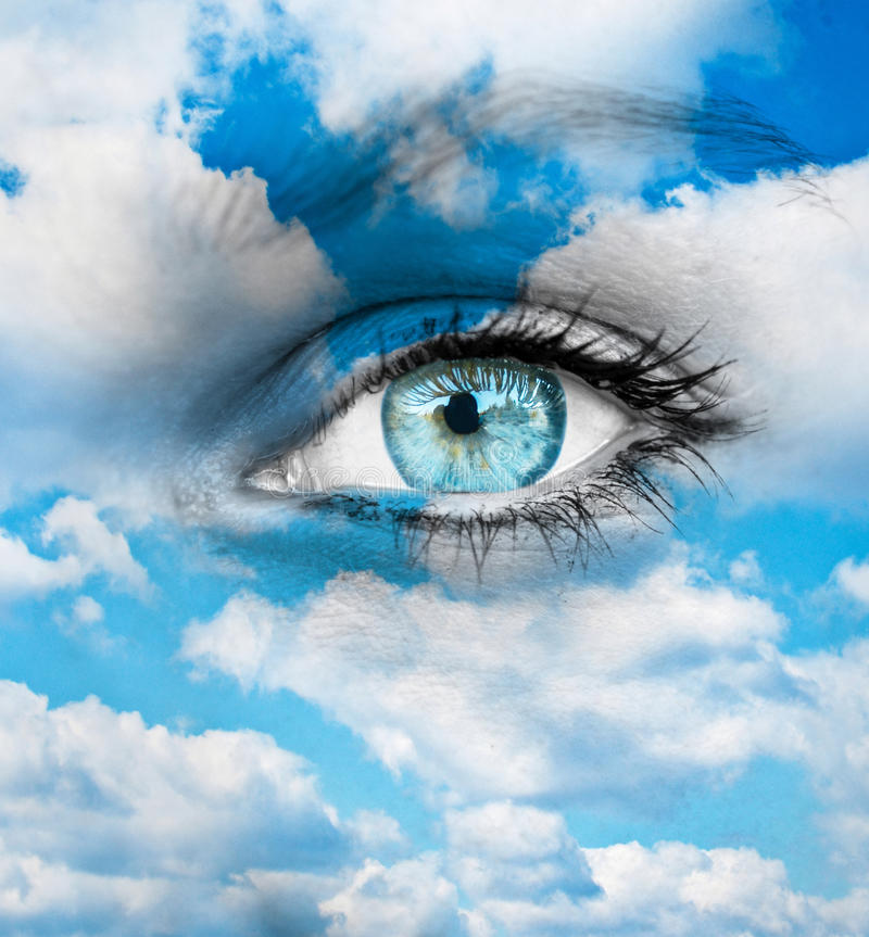 Beautiful blue eye against blue clouds - Spiritual concept royalty free stock image