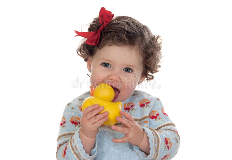 Beautiful blue-eyed baby sucking a rubber duck royalty free stock images