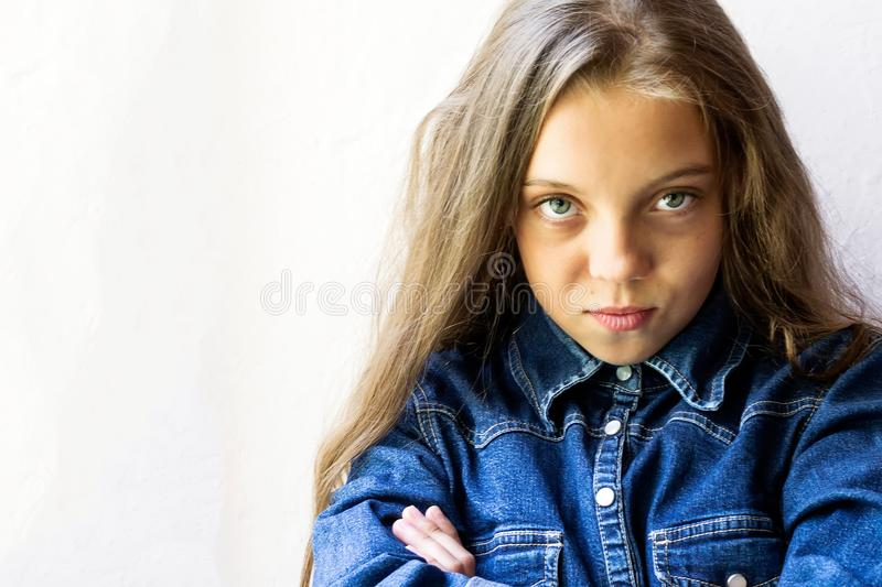 Beautiful blue-eyed, blonde teenage girl in jeans shirt. On a light background. Copy space. Close-up. Beauty and fashion. stock photo
