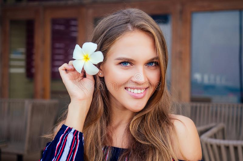 Beautiful blue eyed female model on the beach . perfectly clean skin face with frangipani flower healthy model girl with. Wellness body .happy tourist woman on stock photo