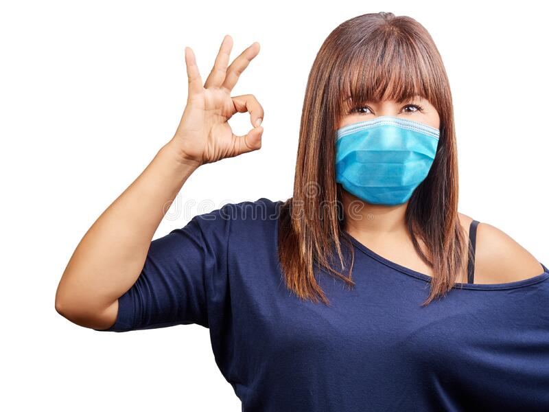 Beautiful blue eyes woman face wearing surgical mask to protect her from getting ill gesture ok. Virus protection stock images