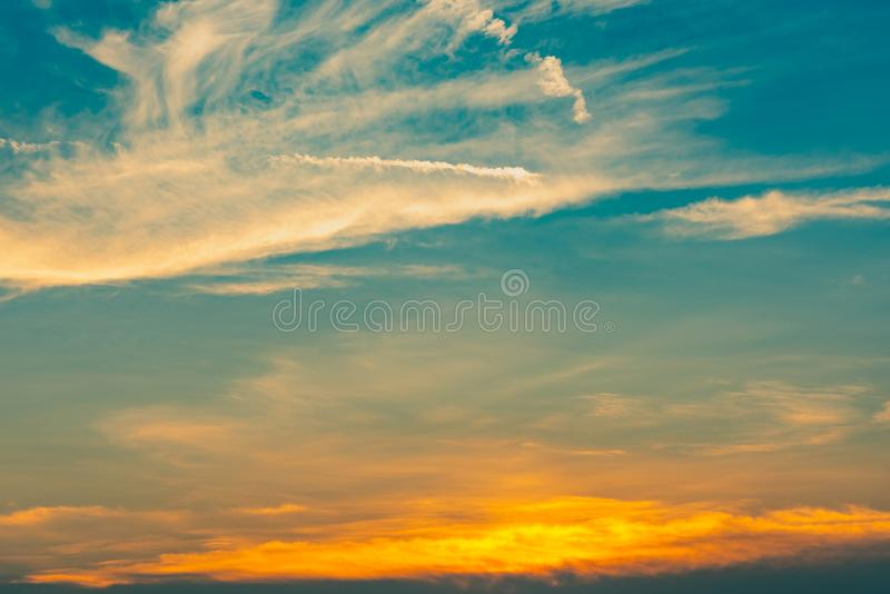 Beautiful blue and golden sky and clouds abstract background. Yellow-orange clouds on sunset sky. Warm weather background. Art royalty free stock images