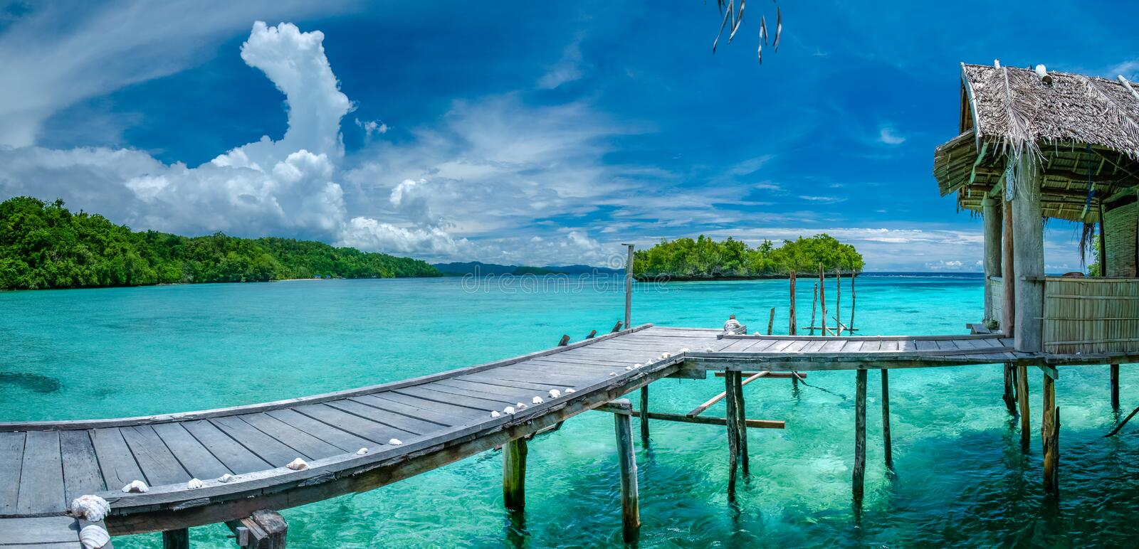 Beautiful Blue Lagoone with some Bamboo Huts, Kordiris Homestay, Palmtree in Front, Gam Island, West Papuan, Raja Ampat. Indonesia royalty free stock photos