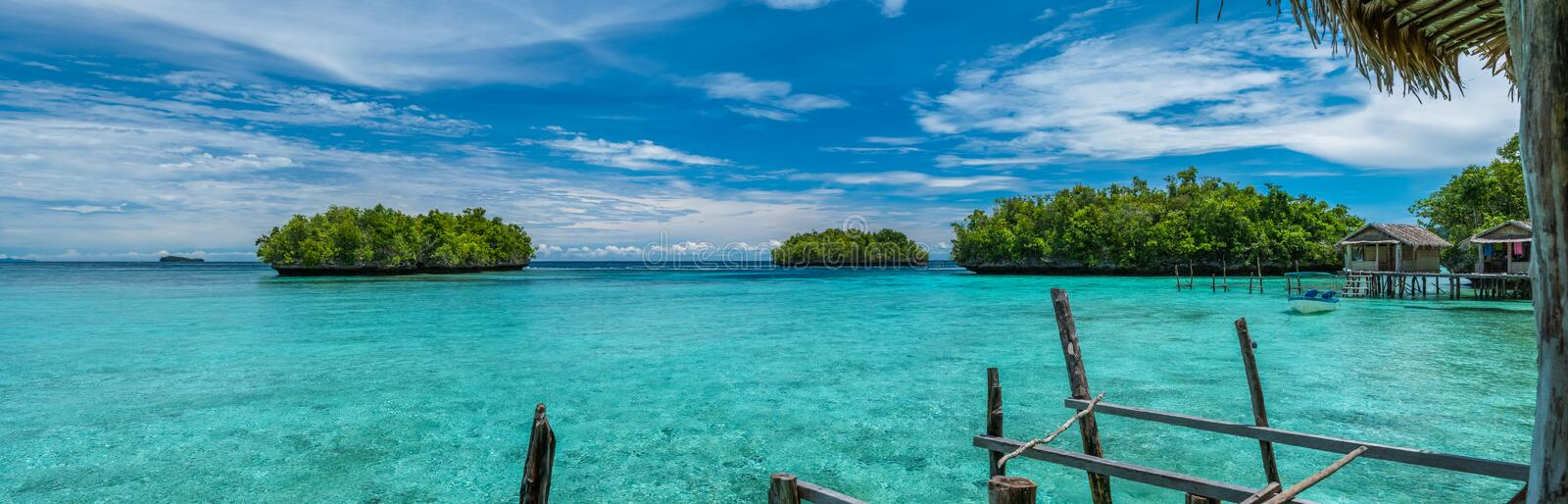Beautiful Blue Lagoone with some Bamboo Huts, Kordiris Homestay, Palmtree in Front, Gam Island, West Papuan, Raja Ampat. Indonesia stock photography