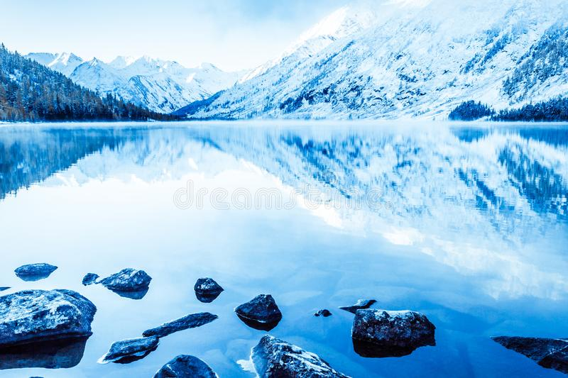 Beautiful blue lake in the mountains. Flat mirror surface of the water under the clouds. royalty free stock photo