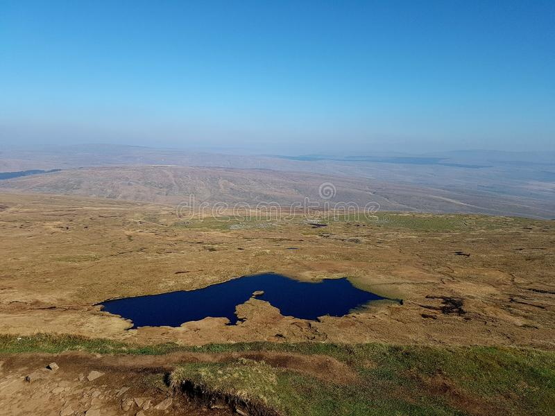 Mountain top lake. Beautiful blue lake from the top of a green brown mountain stock photos
