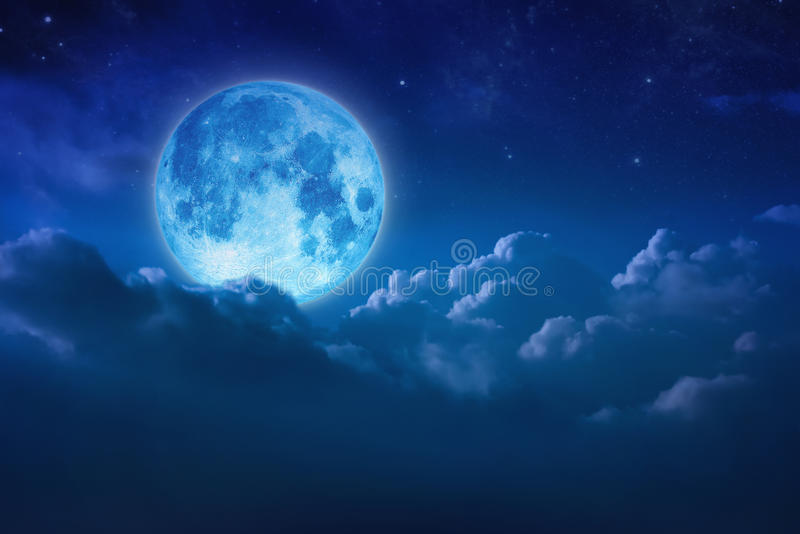 Beautiful blue moon behind cloudy on sky and star at night. Outdoors at night. Full lunar shine moonlight over cloud at nighttime royalty free stock images