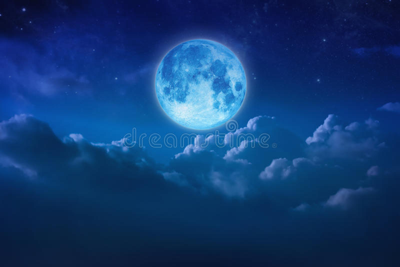 Beautiful blue moon behind cloudy on sky and star at night. Outdoors at night. Full lunar shine moonlight over cloud at nighttime royalty free stock image