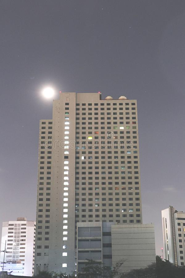 building and Beautiful blue night sky witha little bit clouds and fullmoon an stock images