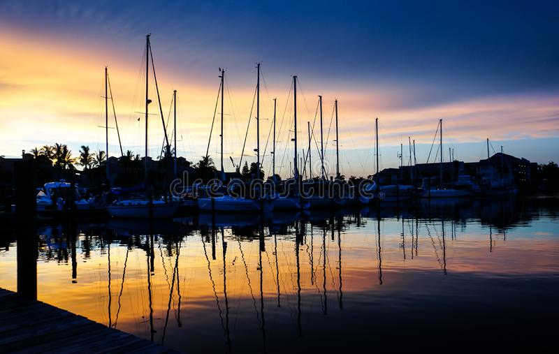 Blue and pink sunset in a Florida marina with Palm Trees and sailboats reflecting on the water stock images