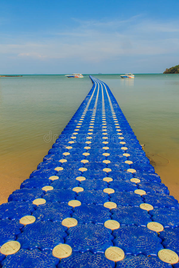 Beautiful blue pontoon made from plastic floating in the sea, rotomolding jetty, a landing stage or small pier at which boats can stock photos