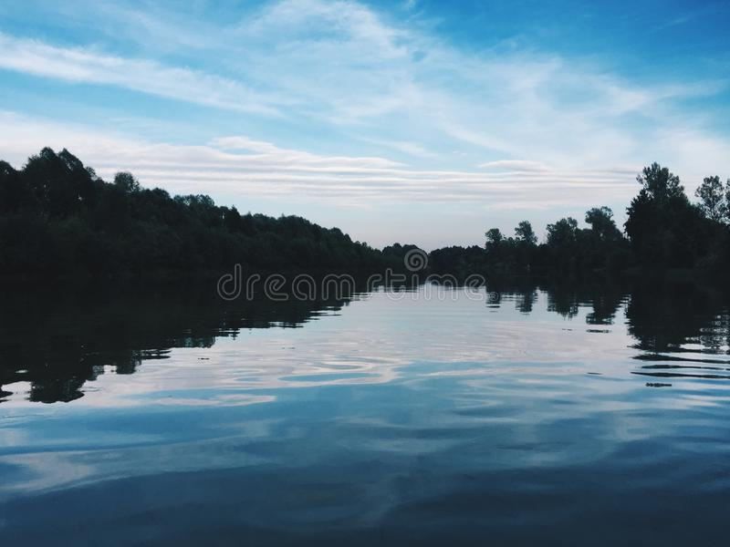 Beautiful blue river with reflecting clouds in the water in the middle of green. Forests with trees stock image