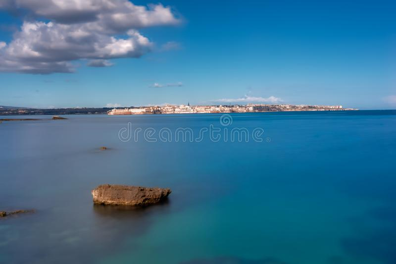 Beautiful blue sea with rock formations under the white clouds during daytime. A beautiful blue sea with rock formations under the white clouds during daytime royalty free stock photography