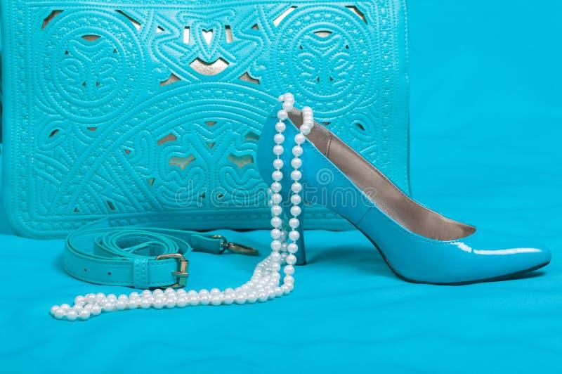 Beautiful blue shoes and handbag, pearls royalty free stock image