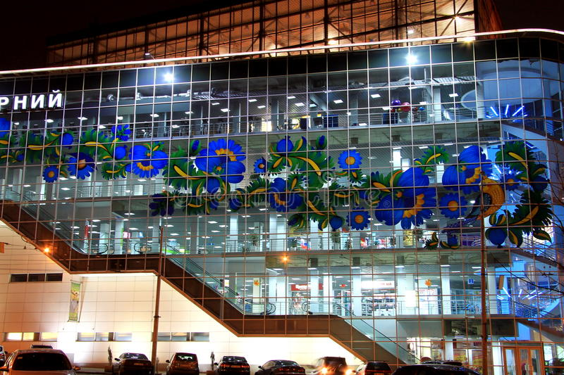 Beautiful blue shopping mall, decorated with Petrikov painting - a national Ukrainian ornament on the facade, in evening. stock photography