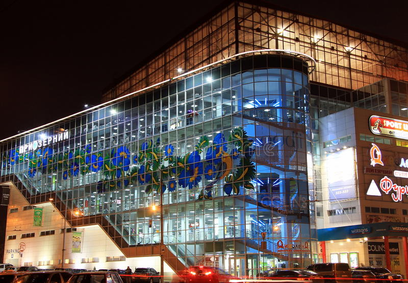 Beautiful blue shopping mall, decorated with Petrikov painting - a national Ukrainian ornament on the facade, in evening royalty free stock photo