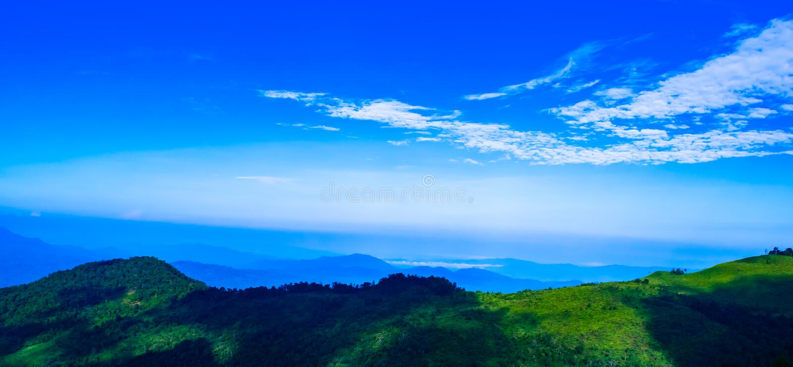 Beautiful blue sky background over mountains with white cloudy in the morning at Phu Soi Dao, Uttaradit northern of Thailand. stock photo