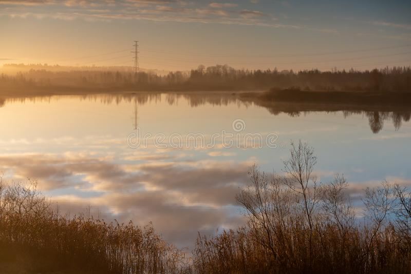 Beautiful blue sky and cloud reflection in the water. Beautiful autumn morning in the countryside near the lake, fog in the distance, beautiful blue sky and royalty free stock photo