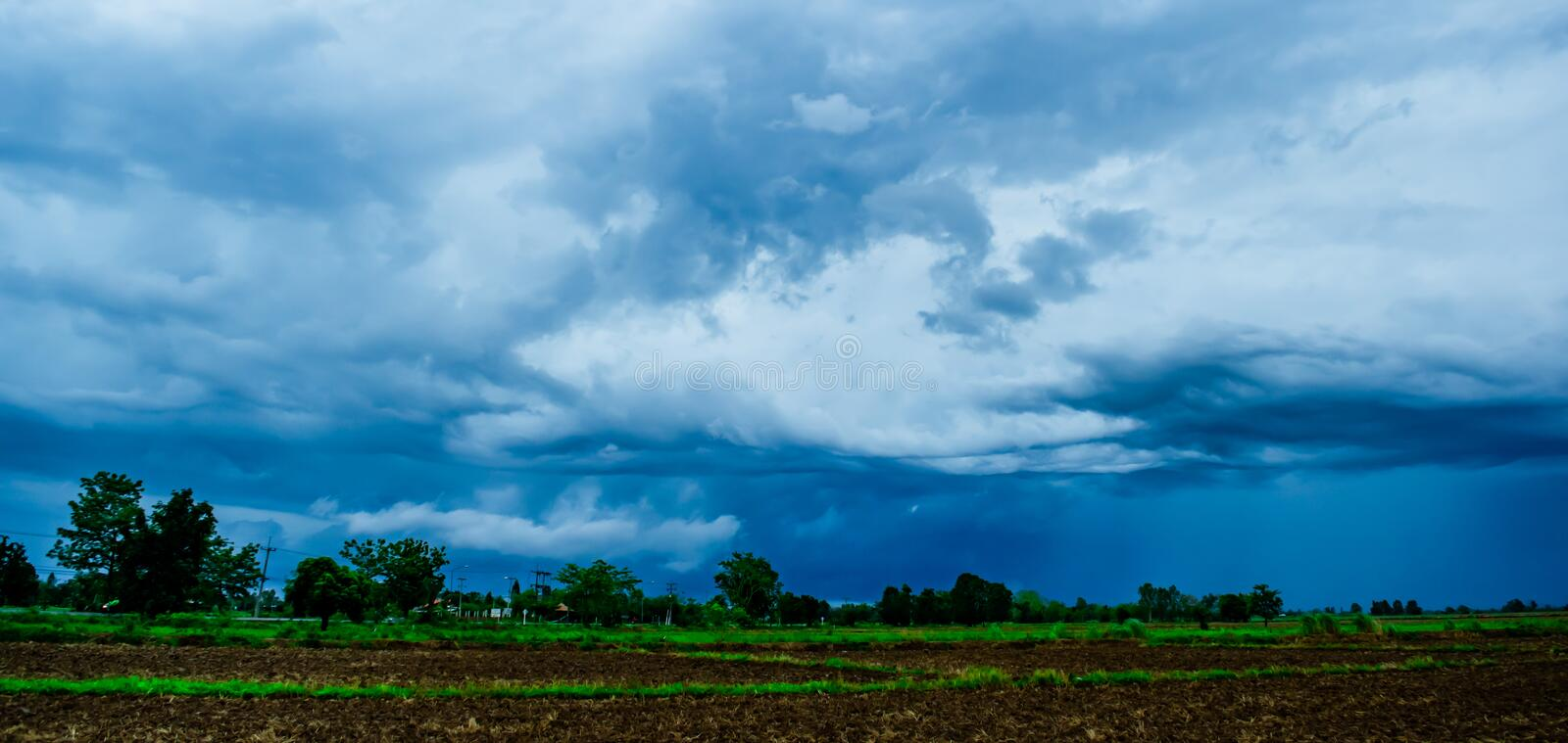 Beautiful blue sky and many white cloudy background over the green field in countryside landscape on rainy season. Beautiful blue sky background and white stock photography