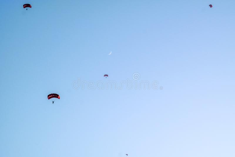 Beautiful blue sky and moon with Skydivers parachuting in Dubai. UAE royalty free stock photography