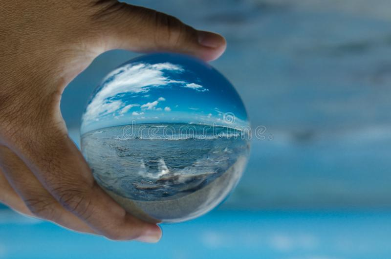 Beautiful Blue sky at oceanside in clear crystal glass ball. Beautiful Blue sky at oceanside in clear crystal glass ball by left male hand holding royalty free stock images