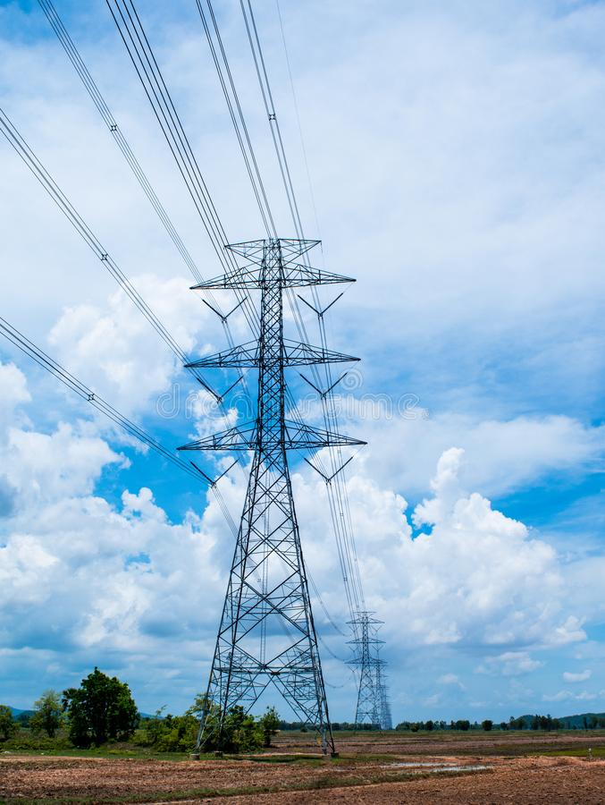 Beautiful white cloudy sky and blue sky background over the high voltage pole in the countryside landscape, look fresh and relax. Beautiful blue sky over high royalty free stock image