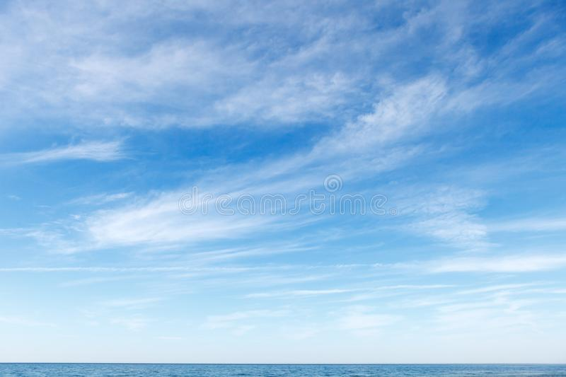 Beautiful blue sky over the sea with translucent, white, Cirrus clouds. The horizon line royalty free stock photos
