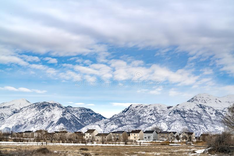 Beautiful blue sky with puffy clouds over homes and mountain in winter royalty free stock images
