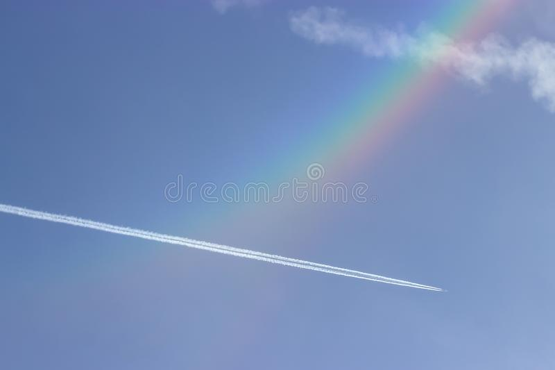 Beautiful blue sky, rainbow and small plane stock photo