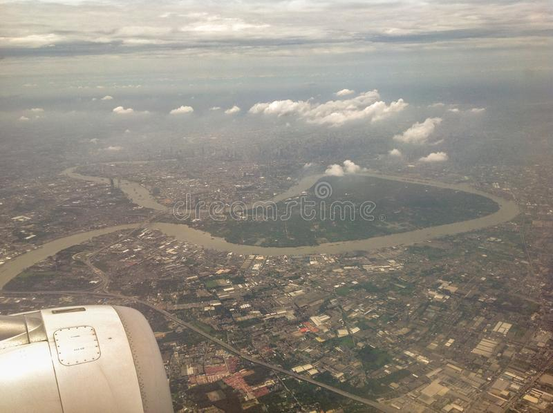The beautiful blue sky, white cloud, land and house can be visible from the plane. In Thailand stock photos