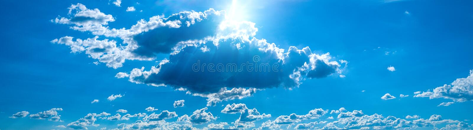 Beautiful blue sky with white clouds and sunlight. Background abstract panorama stock image