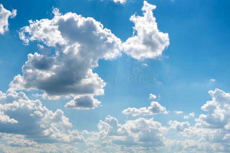 Beautiful blue sky with white clouds and a thin horizon line. Rays The sun breaks through the clouds. Space bright summer day outdoors light freedom heaven royalty free stock photo