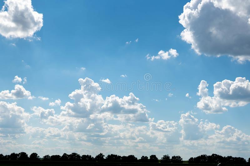 Beautiful blue sky with white clouds and a thin horizon line. Rays The sun breaks through the clouds. Space bright summer day outdoors light freedom heaven royalty free stock image