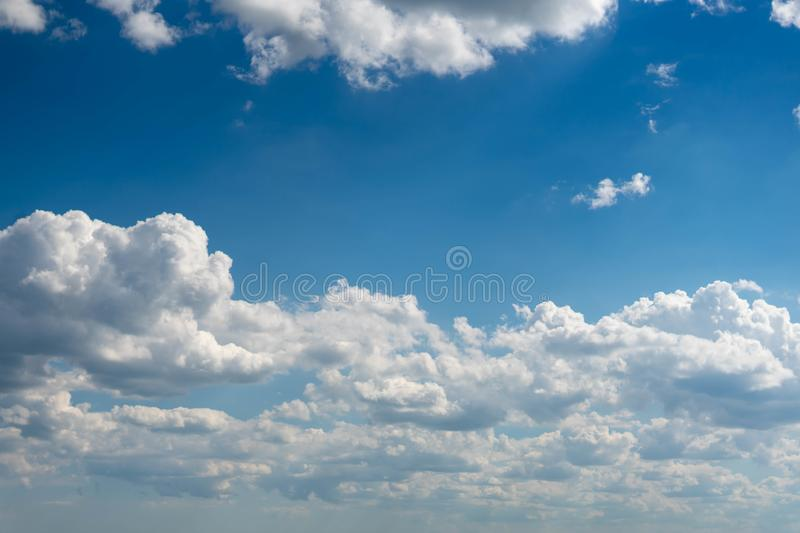 Beautiful blue sky with white clouds and a thin horizon line. Rays The sun breaks through the clouds. Space bright summer day outdoors light freedom heaven stock photography