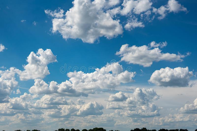 Beautiful blue sky with white clouds and a thin horizon line. Rays The sun breaks through the clouds. Space bright summer day outdoors light freedom heaven stock images