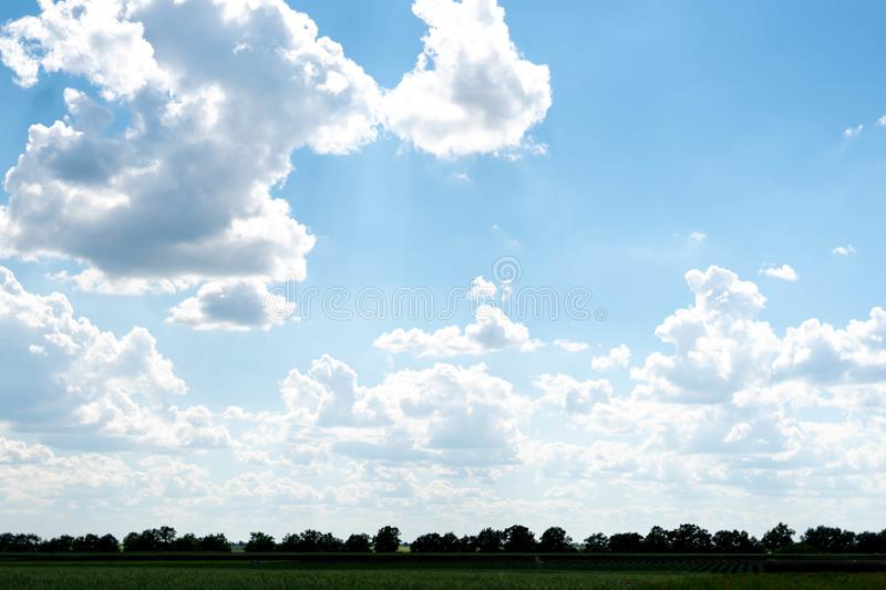 Beautiful blue sky with white clouds and a thin horizon line. Rays The sun breaks through the clouds. Space bright summer day outdoors light freedom heaven stock image