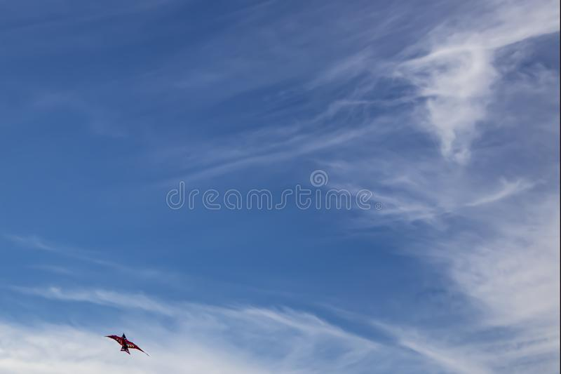 Beautiful blue sky with wispy white clouds background with bright colored bird kite in lower left one third - room for copy.  royalty free stock photo