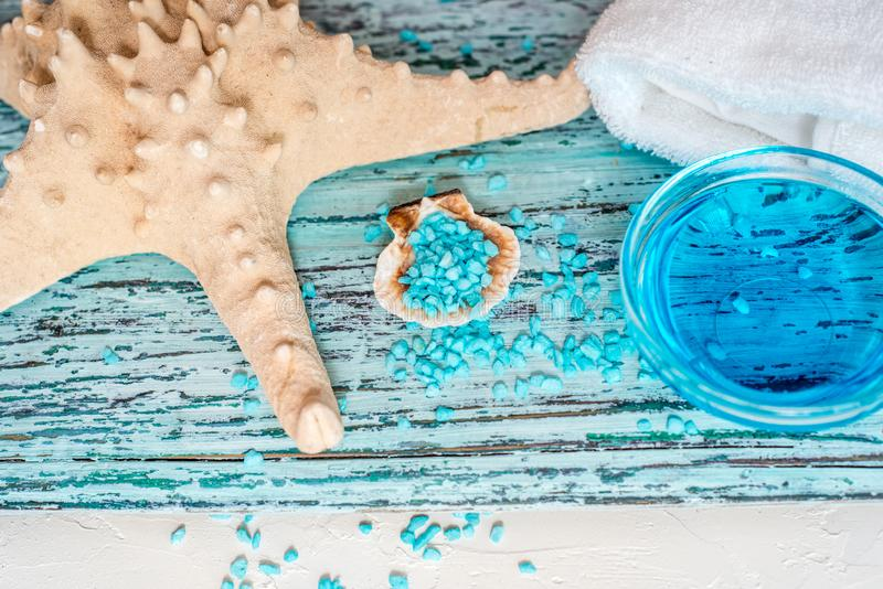 Beautiful blue spa composition. blue sea salt, liquid soap, starfish, shells and a white bath towel stock photo