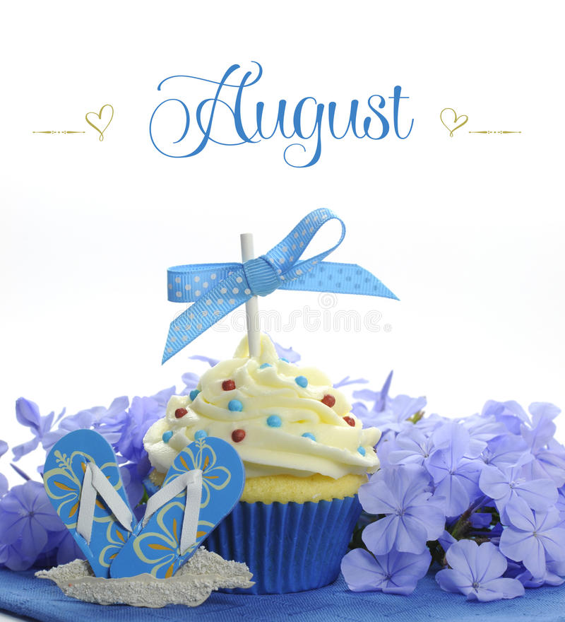 Beautiful blue Summer holiday theme cupcake with seasonal flowers and decorations for the month of August. With sample text or copy space for your text here stock photo