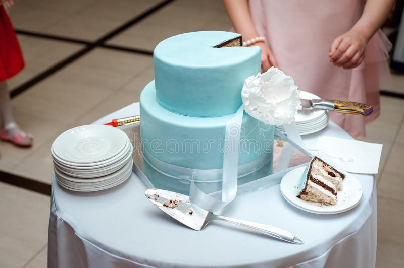 A beautiful blue wedding cake is being cut by the Newlyweds. While ceremony stock images