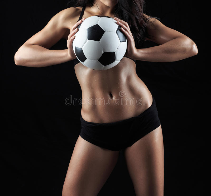 Beautiful body of fitness model holding soccer ball royalty free stock photography